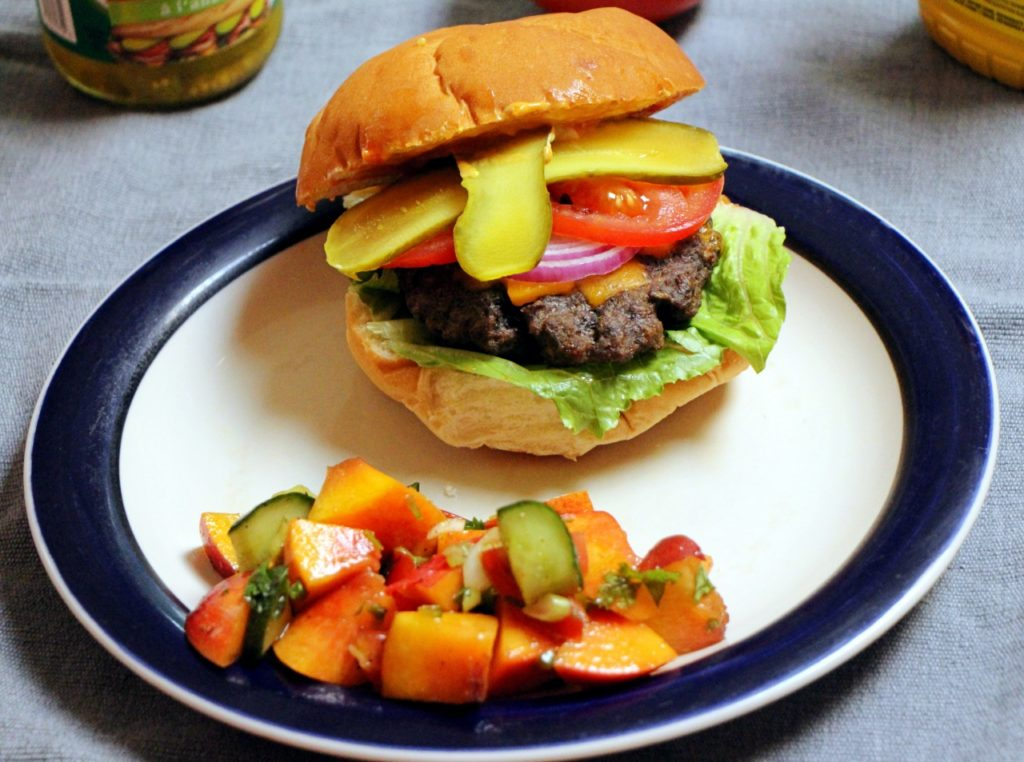 Delicious Beef burger with peach, tomato and cucumber salad